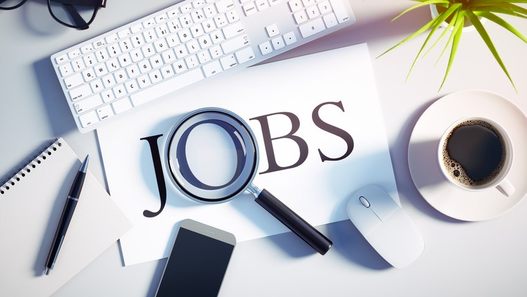 Top view of a white desktop with magnifying glass over the word JOB